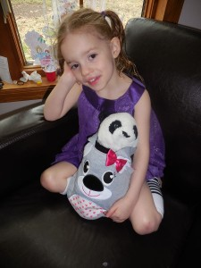 In her new purple dress with her koala bag.